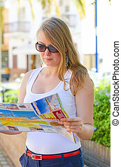 Young blonde woman with a map in the street