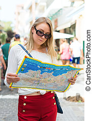 Young blonde woman with a map in the street.