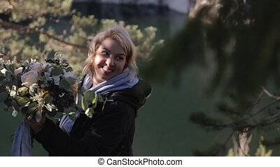 Young blonde woman with bouquet in forest near lake