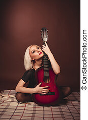 Young blonde woman with guitar