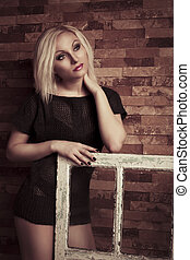 Young blonde woman with old window