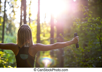Young blonde woman working out with dumbbells in beautiful nature
