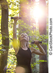Young blonde woman working out with dumbbells outside in forested area