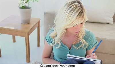 Young blonde woman writing in a notebook