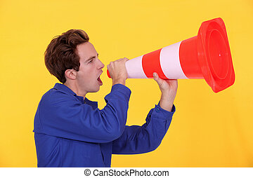 young blue collar shouting in construction cone