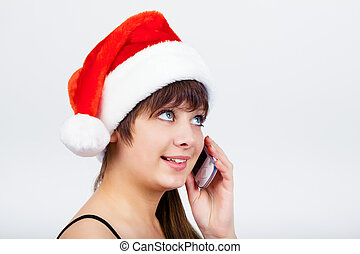 blue-eyed beautiful girl in santa hat with phone