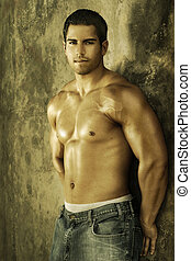 Young bodybuilder against wall - Young muscular male against...