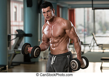 Young Bodybuilder Exercising Biceps With Dumbbells