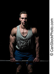 young bodybuilder posing on black background
