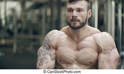 Young bodybuilder posing standing in gym indoor. Hardener...