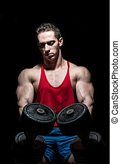 young bodybuilder posing with dumbbell at the bench on black background