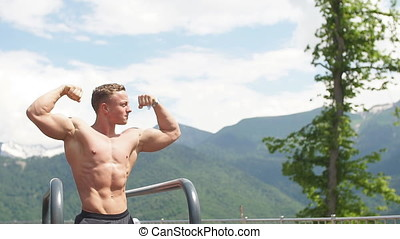 Young bodybuilder showing muscles shape outdoors -...