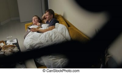 Young Bored Couple Watching TV