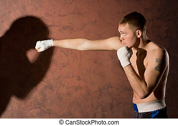 Young boxer punching his opponent - Side view of a young ...