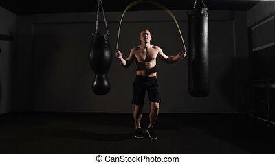 Young boxer training with a skipping rope as he practices his endurance,