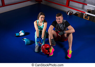 Young boxing couple sitting near lying boxing gloves and helmet