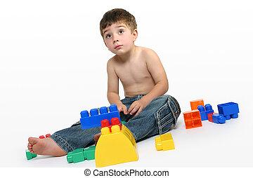Young boy amongst building blocks