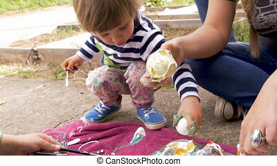 Young boy and girl coloring easter eggs and making a mess with their mom