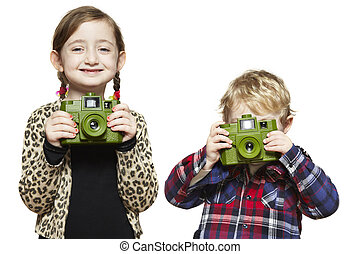 Young boy and girl each holding a camera