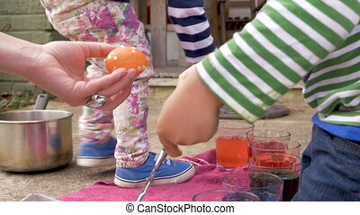 Young boy and girl help their mother coloring easter eggs...
