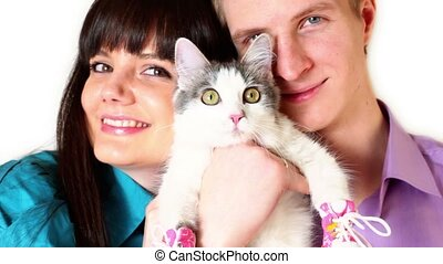 Young boy and girl hold cat in pink shoes