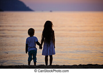 Young boy and girl holding hands while standing on beach