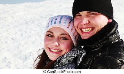 young boy and girl hugging stand outdoors in winter