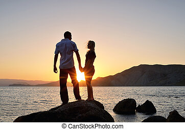 Young boy and girl look at each other, hand in hand on beach