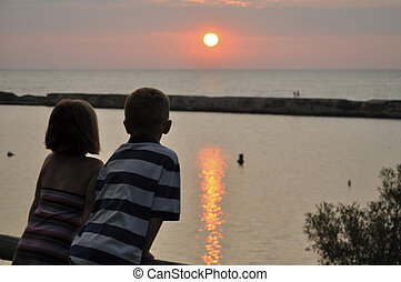 young boy and girl overlooking sunset and water