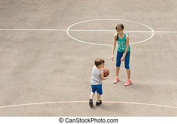 Young boy and girl playing basketball