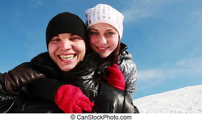 boy and girl standing outdoors in winter, she hugs it from behind neck