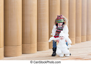 Young boy and his baby sister on a walk next to a modern building entrance with pillars