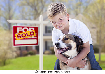 Young Boy and His Dog in Front of Sold For Sale Sign and House