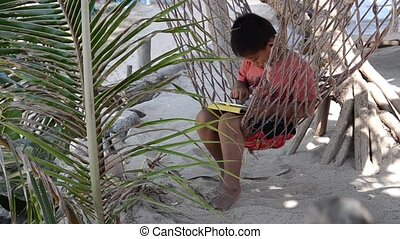 young boy and his tablet - thai child on hammock using...