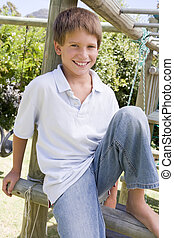 Young boy at a playground smiling