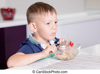 Young Boy at Breakfast Table Eating Bowl of Cereal