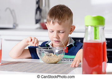 Young Boy at Breakfast Table Eating Bowl of Cereal - Young...