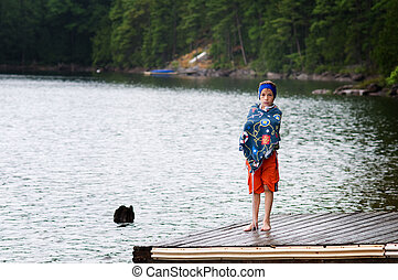 young boy at the lake wearing a swim band to protect his ears