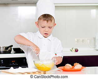 Young boy baking whipping eggs