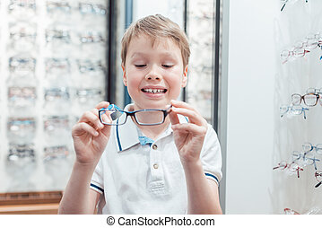 Young boy being very happy with his new eyeglasses in the store
