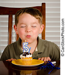 Young boy blowing out his birthday candle