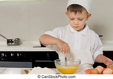Young boy breaking eggs into a mixing bowl