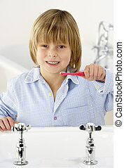 Young Boy Brushing Teeth at Sink