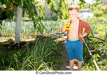 Young boy carrying a spade