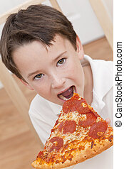 Young Boy Child Eating Slice of Pizza