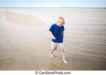 Young Boy Child Walking in the Sand off the Ocean Shore at the Beach on a Summer Day