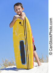 Young Boy Child With Surfboard At The Beach