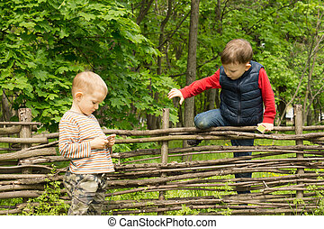Young boy climbing over a rustic wooden fence in rural woodland as his friend stands waiting for him on the other side