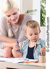 Young boy coloring with wax crayons