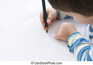 Young boy concentrates while drawing with a green pencil